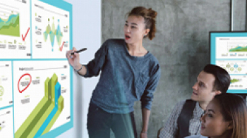 Two people using pointing at a projected screen in a work environment.